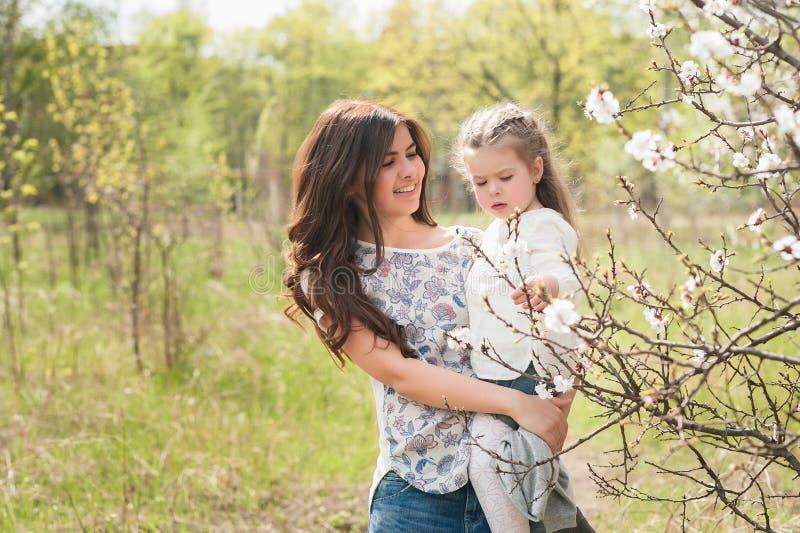 La mamá abraza a la hija de los besos en el jardín enorme de la primavera imagenes de archivo