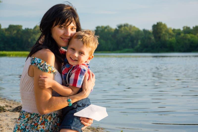 La mamá abraza su hijo, risas y controles un aeroplano de papel cerca de un río en la puesta del sol imágenes de archivo libres de regalías