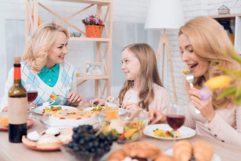 La mamá, la abuela y la niña están cenando juntas en casa foto de archivo