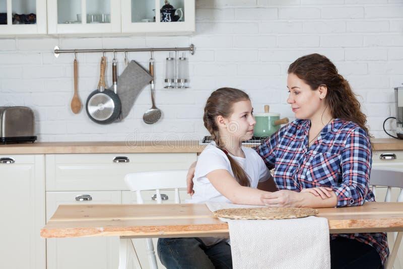 La mamá adulta tiene una conversación seria con su hija adolescente, hablando en la cocina en la tabla, espacio de la copia fotografía de archivo libre de regalías