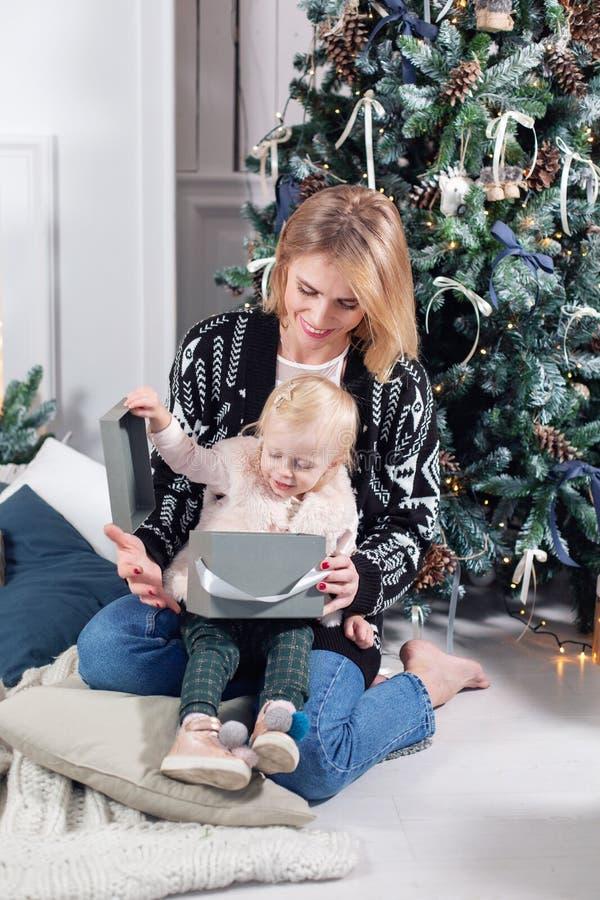La mamá alegre y su bebé lindo de la hija abren un regalo Padre y pequeño niño que se divierten cerca del árbol de navidad dentro foto de archivo