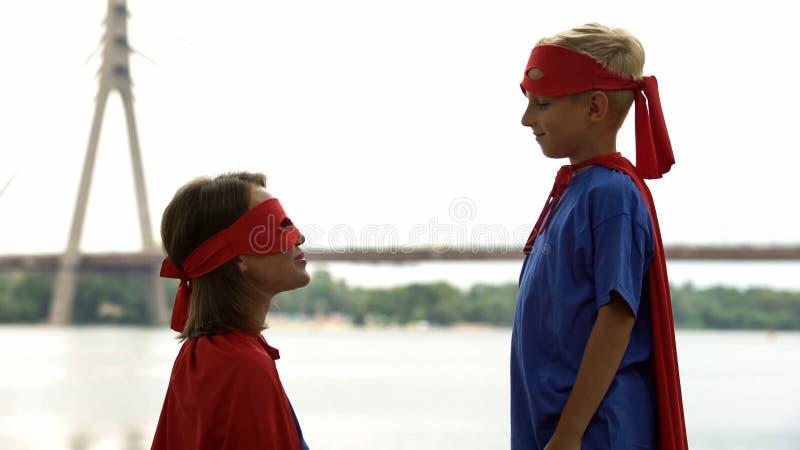La mamá apoya al hijo en el juego del super héroe, psicoterapia para que el muchacho haga frente a problemas fotos de archivo libres de regalías