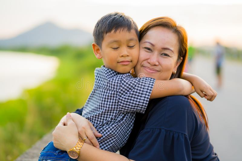 La mamá asiática abraza a su hijo joven cariñosamente en la puesta del sol con el backg de la naturaleza foto de archivo
