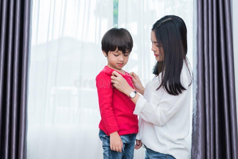 La mamá asiática joven vestida encima de la camisa del hijo para prepararse va a la escuela fotografía de archivo