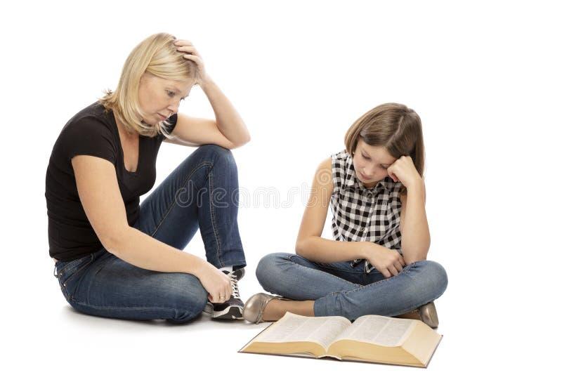 La mamá ayuda a su hija adolescente a aprender las lecciones, aisladas en el fondo blanco imagen de archivo