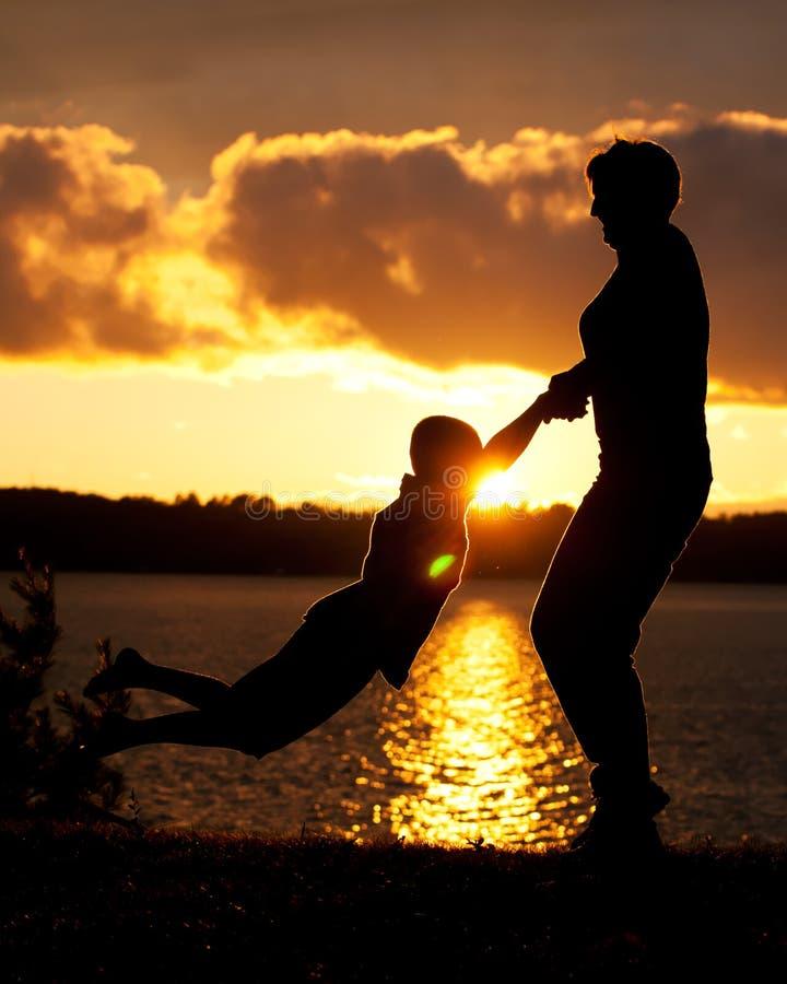 La mamá balancea al hijo en puesta del sol imagen de archivo libre de regalías