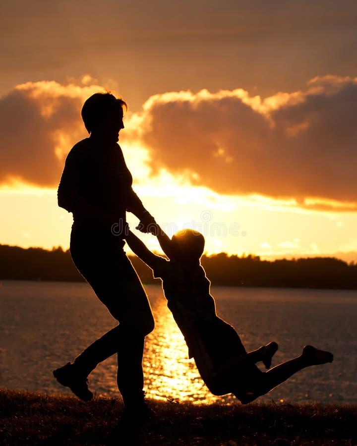 La mamá balancea al hijo en puesta del sol imagen de archivo