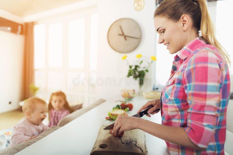 La mamá cocina en la cocina mientras que su juego de niños al lado de ella en el sofá fotografía de archivo libre de regalías