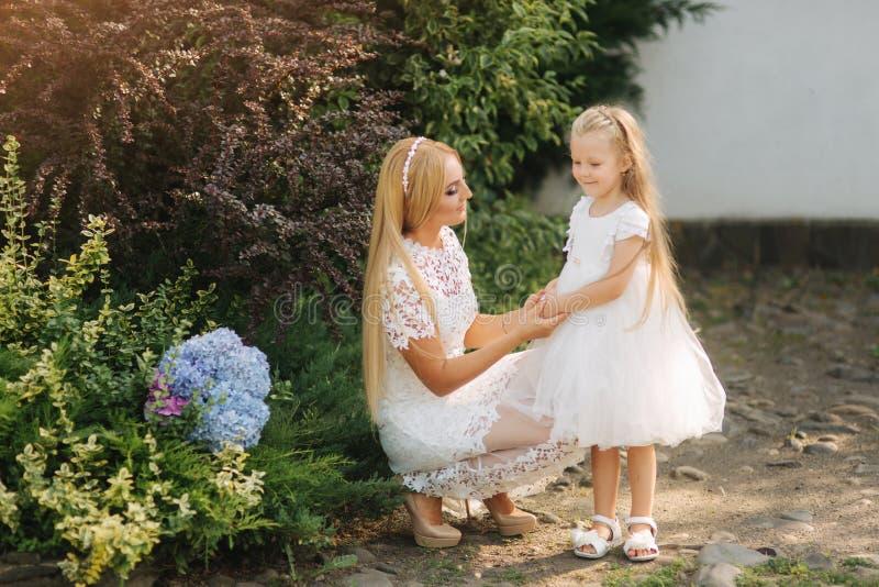 La mamá con la hija en los vestidos blancos pasa tiempo en el parque Hembra del pelo rubio La madre teje el exterior de la hija d foto de archivo libre de regalías