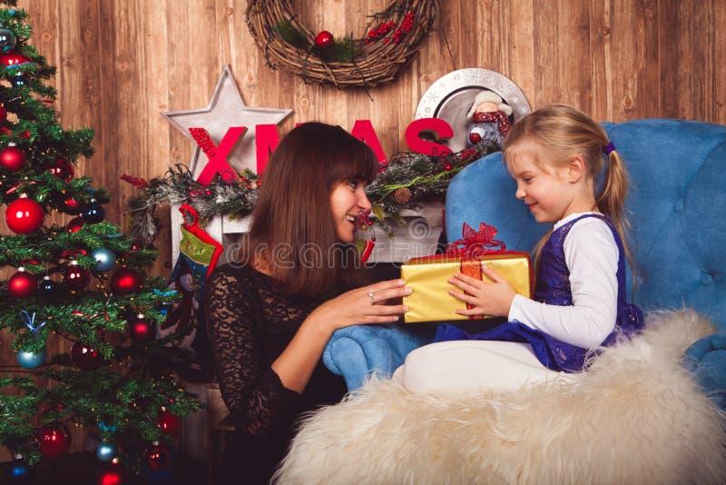 La mamá da el regalo de la hija delante del árbol de navidad fotos de archivo libres de regalías