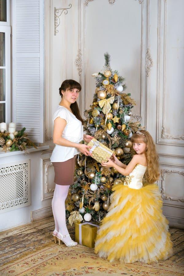 La mamá da a hija un regalo de la Navidad, árbol del nuevo-año fotografía de archivo