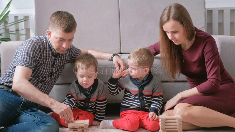 La mamá de la familia, el papá y dos hermanos gemelos juegan juntos la construcción fuera de bloques de madera en el piso imagen de archivo