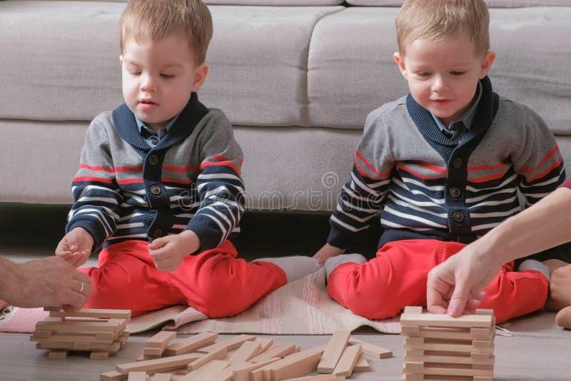 La mamá de la familia, el papá y dos hermanos gemelos juegan juntos la construcción fuera de bloques de madera en el piso Manos d foto de archivo libre de regalías
