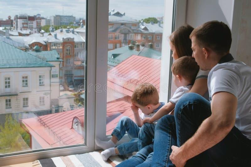 La mamá de la familia, el papá y dos niños de los hermanos gemelos miran hacia fuera la ventana la ciudad fotos de archivo