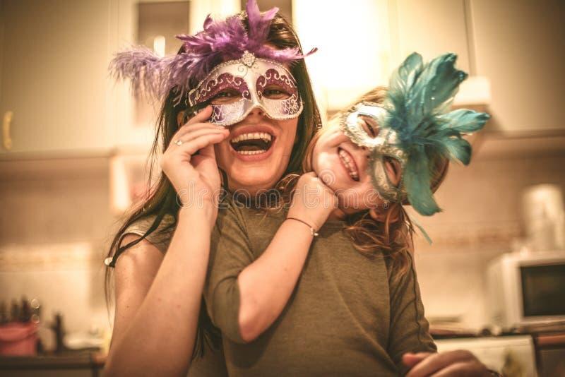 La mamá deja la piel con la máscara La niña tiene juego con la madre foto de archivo libre de regalías