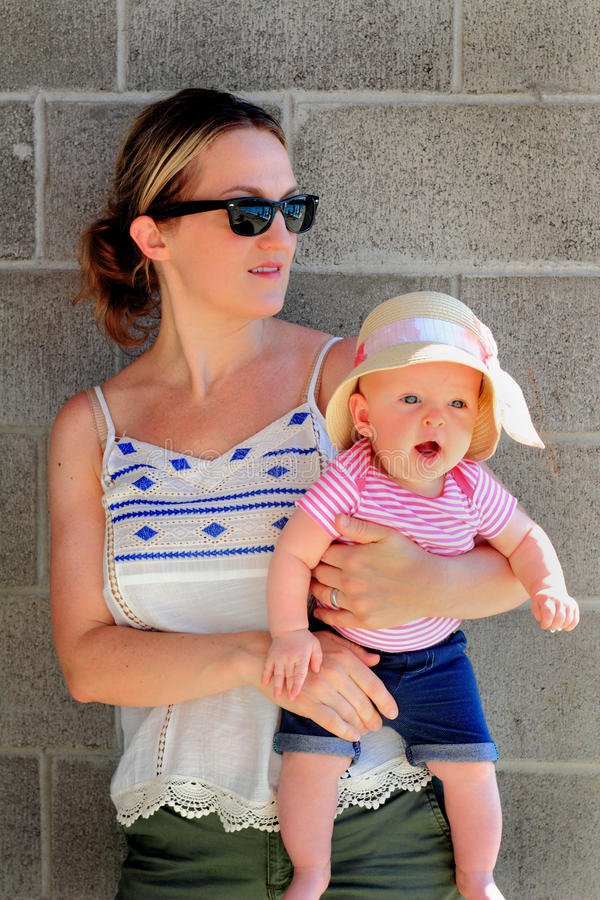 La mamá detiene al bebé joven lindo fotos de archivo