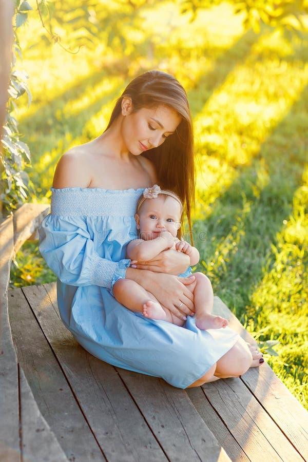 La mamá detiene a un pequeño bebé regordete en los brazos en un día de verano ligero caliente al aire libre fotos de archivo