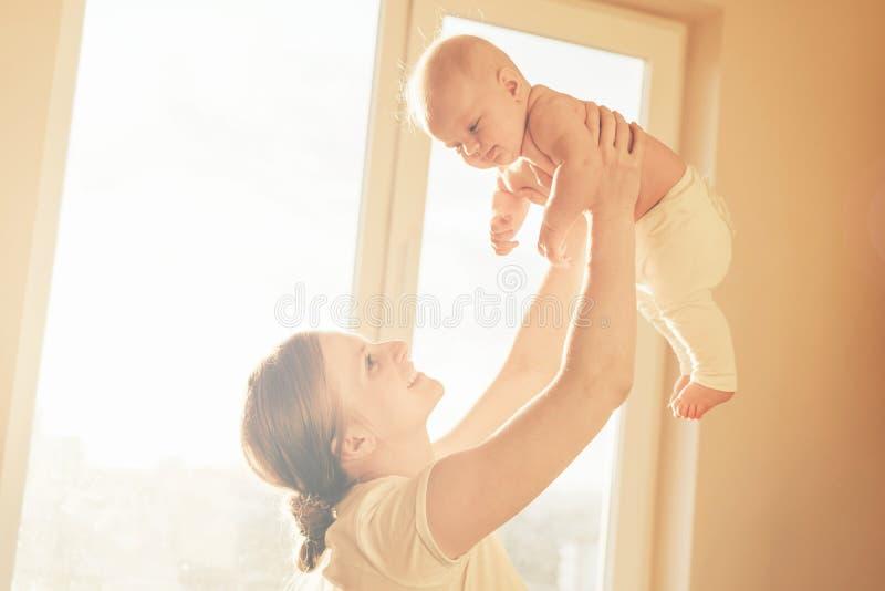 La mamá educó al bebé en sus brazos sobre su cabeza imagen de archivo