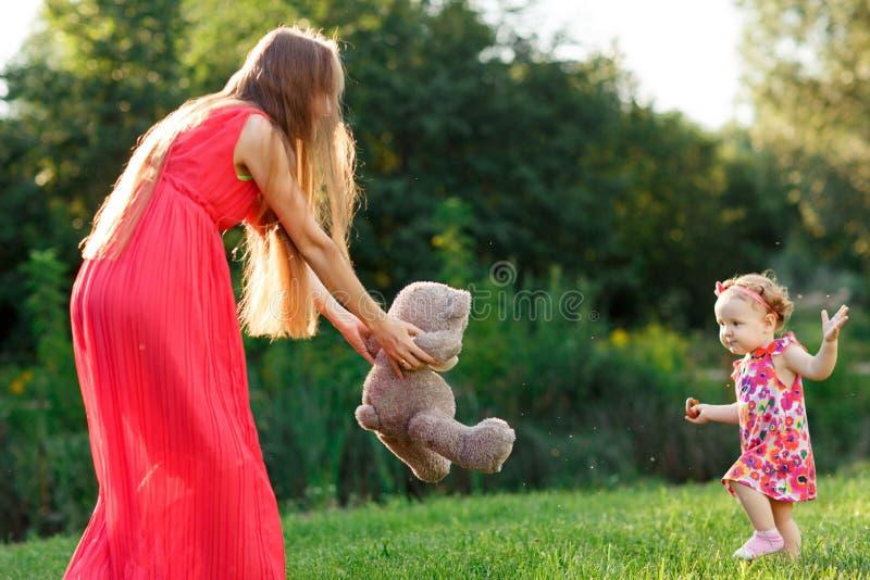 La mamá en tomas del vestido lleva a la pequeña hija en parque del verano foto de archivo
