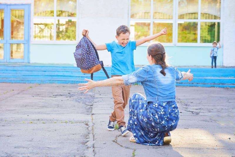La mamá encuentra a su hijo de la escuela primaria funcionamientos alegres del niño en los brazos de su madre un colegial feliz c imagen de archivo