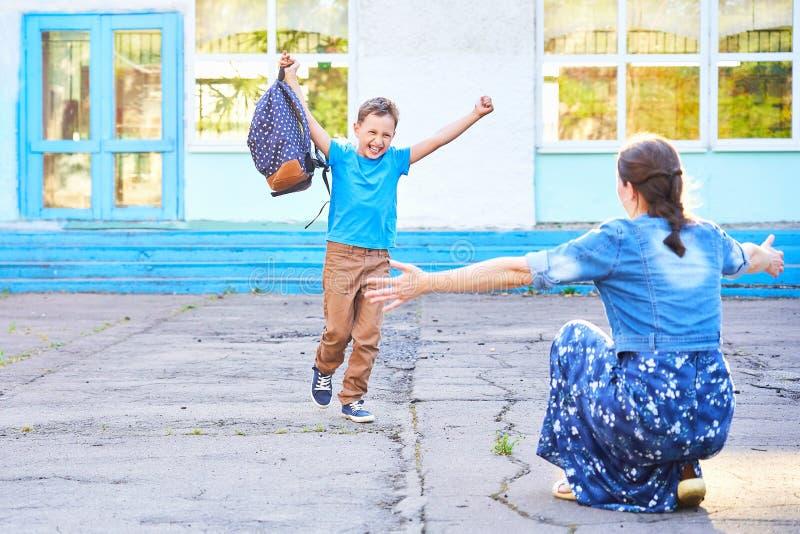 La mamá encuentra a su hijo de la escuela primaria funcionamientos alegres del niño en los brazos de su madre un colegial feliz c fotos de archivo libres de regalías