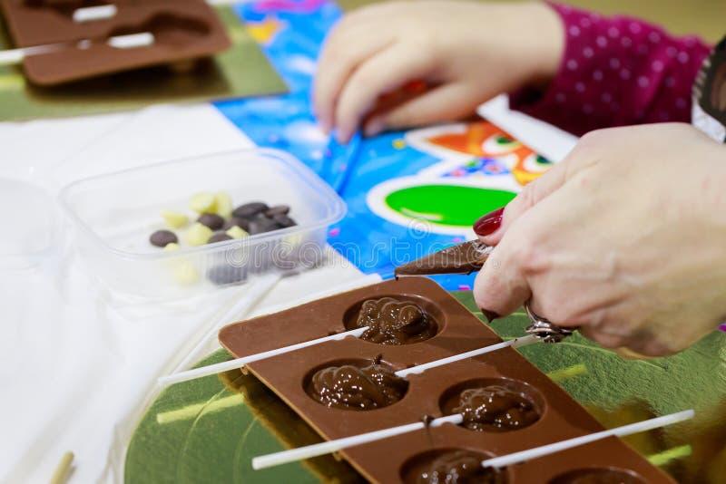 La mamá enseña a su hija a hacer los caramelos de chocolates del chocolate caliente vertiéndolo en moldes fotos de archivo