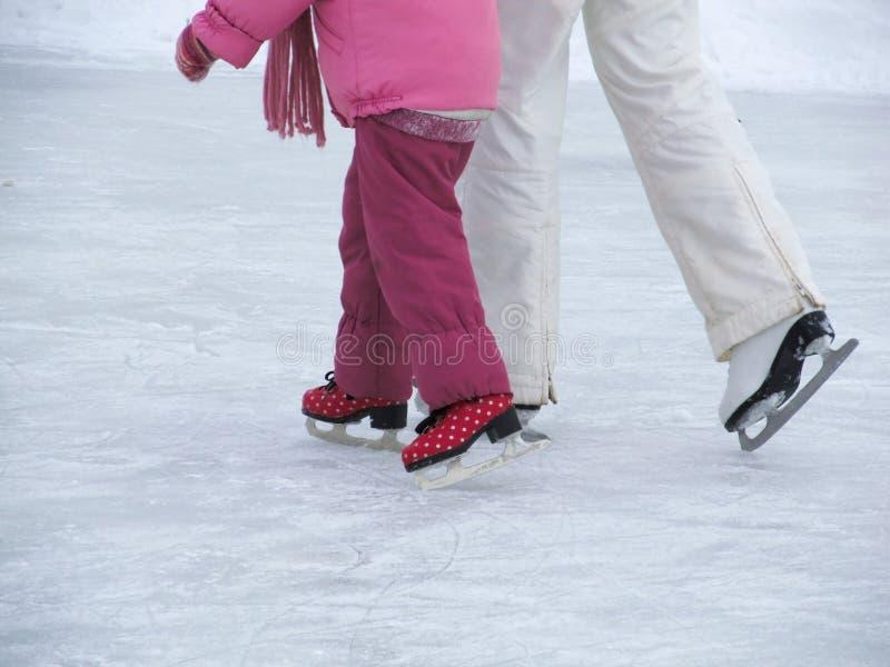 La mamá enseña a su pequeña hija a patinar en la pista en un día de invierno fotos de archivo libres de regalías