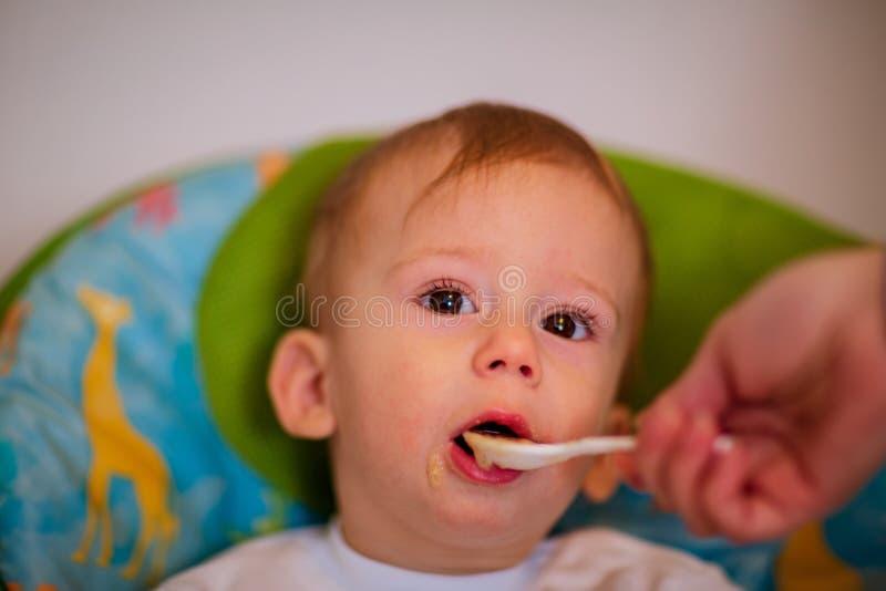 La mamá está alimentando a su bebé en el highchair en casa imagenes de archivo