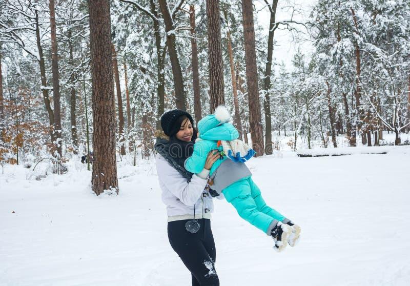 La mamá está circundando en los brazos de un pequeño niño en un parque del invierno imagen de archivo