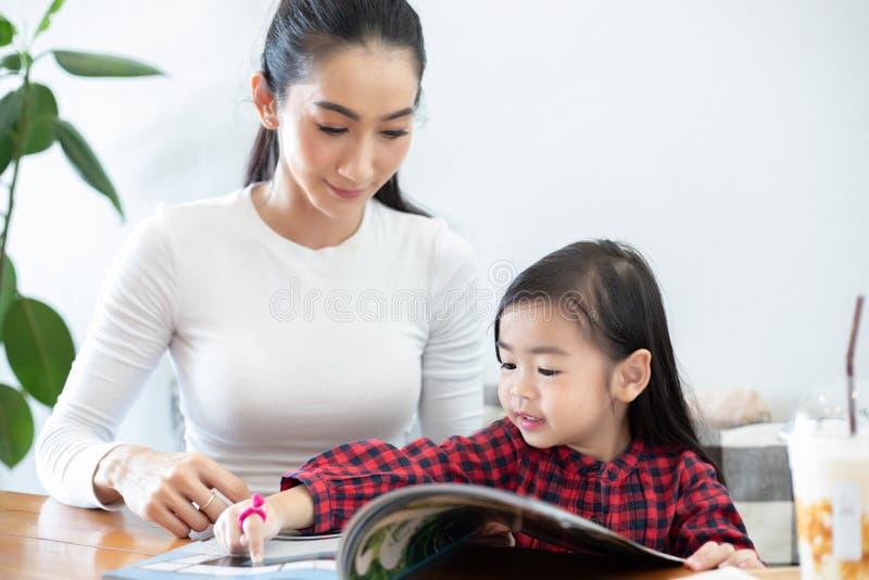 La mamá está enseñando a su hija a leer un libro fotografía de archivo libre de regalías