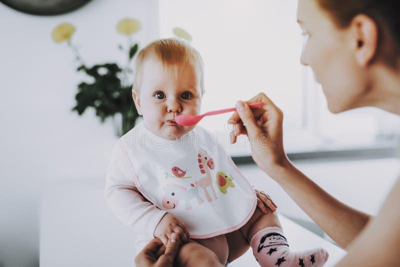 La mamá feliz alimenta al bebé adorable con la cuchara dentro imagen de archivo