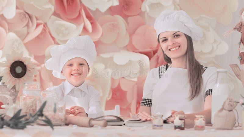 La mamá feliz y su niño bajo la forma de cocineros preparan una cena festiva imágenes de archivo libres de regalías