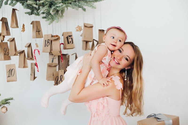La mamá hermosa con la pequeña hija en rosa viste jugar cerca de la decoración de la Navidad fotos de archivo libres de regalías