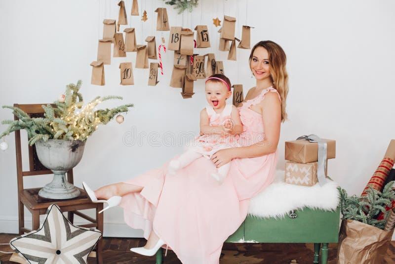 La mamá hermosa con la pequeña hija en rosa viste jugar cerca de la decoración de la Navidad imagenes de archivo