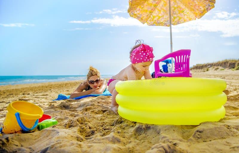 La mamá inflable de la piscina del amarillo de los juegos del bebé la comprueba que toma el sol en la toalla de playa fotos de archivo
