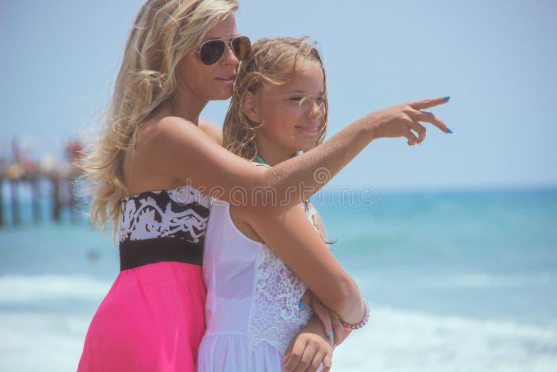 La mamá joven está haciendo señalar el gesto que muestra a algo su hija en el mar fotografía de archivo