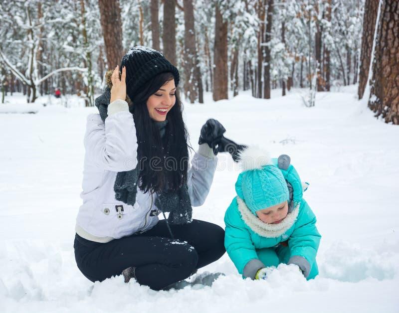 La mamá juega con el niño en la nieve fotos de archivo