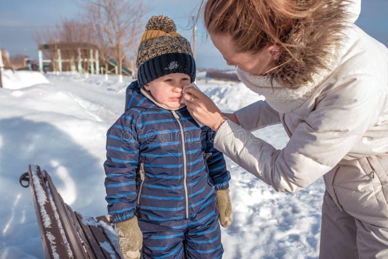 La mamá limpia al hijo de los mocos un niño pequeño En invierno en la ciudad en el banco Servilleta, en ropa caliente Resto en el fotos de archivo