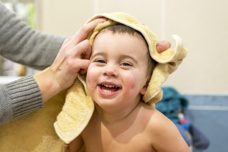 La mamá limpia la toalla de un bebé divertido El niño ríe y disfruta fotografía de archivo libre de regalías