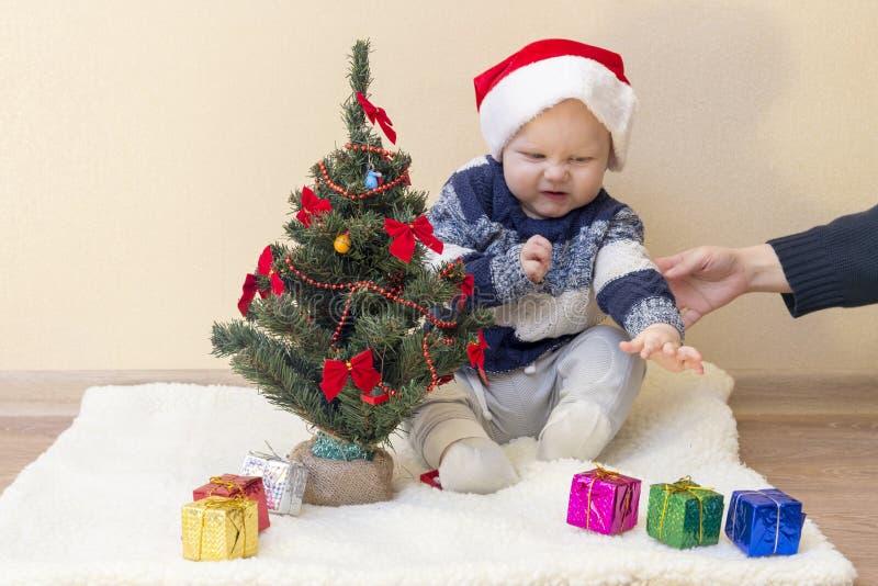La mamá lleva a cabo la mano de un niño contrariedad en un sombrero de Papá Noel imagenes de archivo
