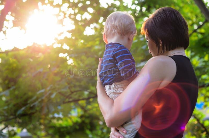 La mamá mantiene a su hijo sus brazos en naturaleza fotografía de archivo