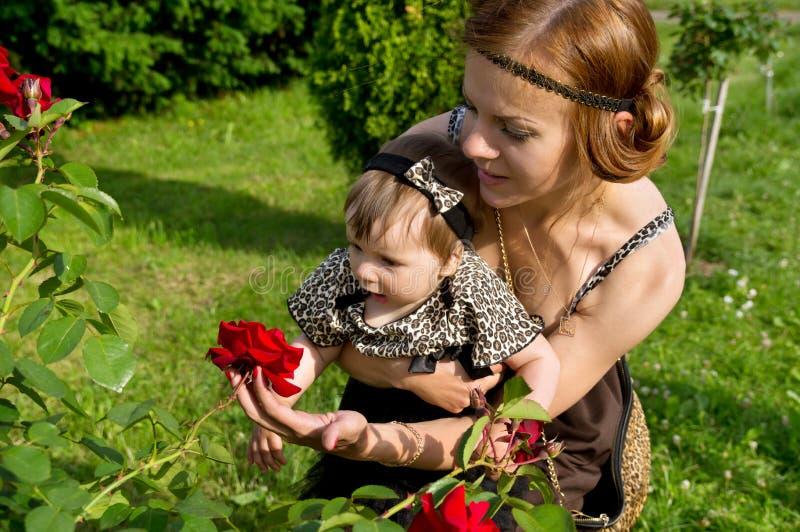 La mamá muestra al niño de flor imagen de archivo libre de regalías