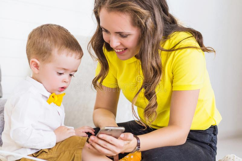 La mamá muestra algo al hijo en el teléfono fotos de archivo