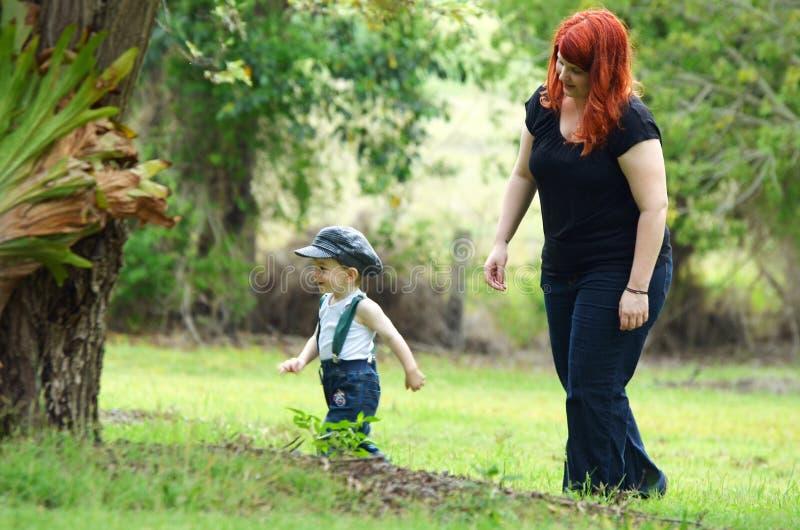 La mamá protectora camina detrás de su pequeño muchacho del hijo del niño en bosque fotografía de archivo libre de regalías