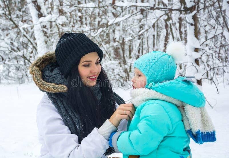 La mamá remedia una ropa al pequeño hijo en un parque del invierno fotos de archivo libres de regalías