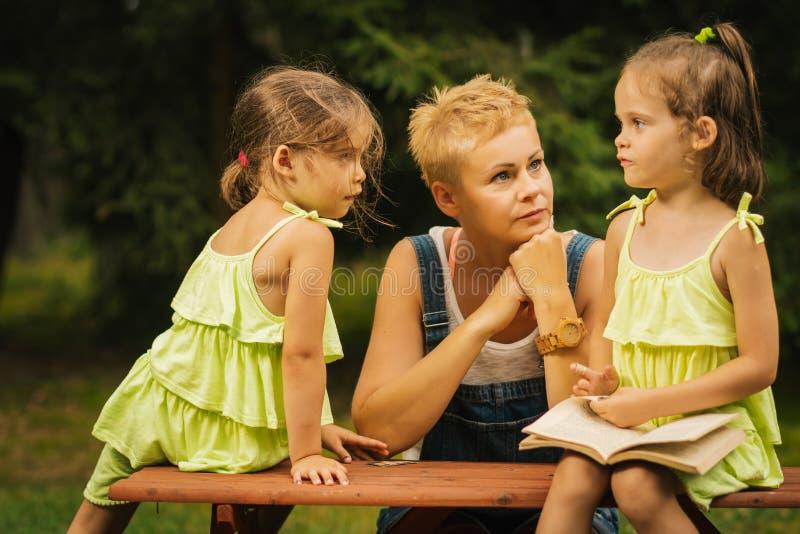 La mamá y dos hijas adorables hablan el uno al otro en el bosque del verano foto de archivo