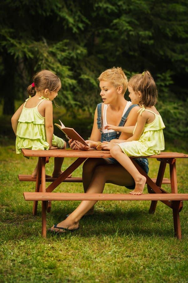 La mamá y dos hijas adorables leyeron un libro en un bosque del verano fotos de archivo libres de regalías