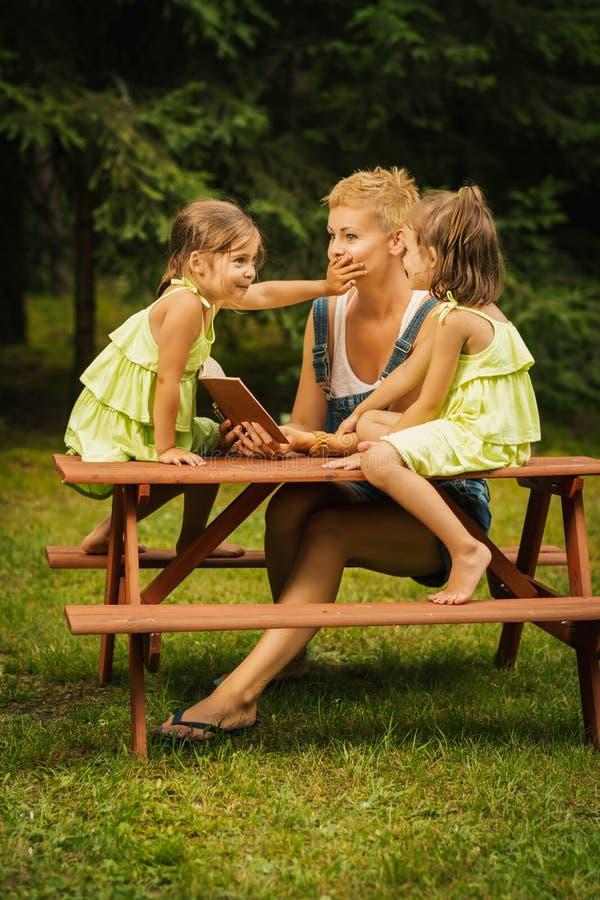 La mamá y dos hijas adorables leyeron un libro en un bosque del verano fotografía de archivo