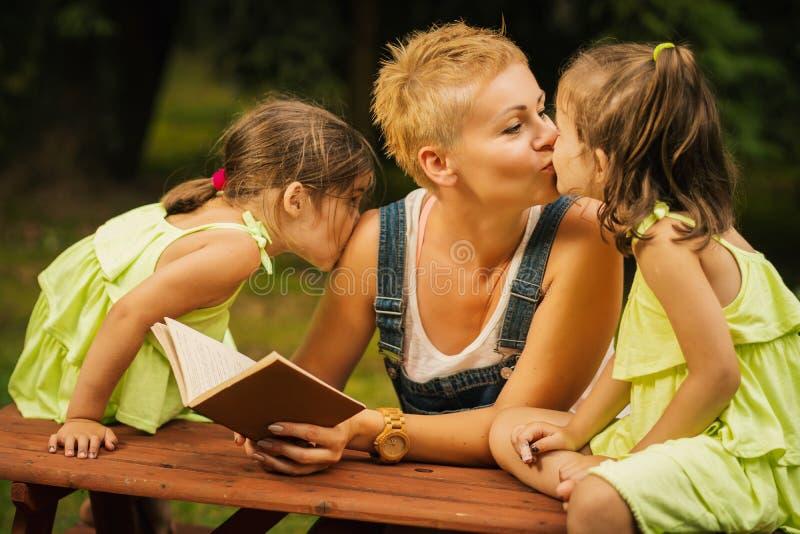La mamá y dos hijas preciosas se dan besos en el bosque del verano imagenes de archivo