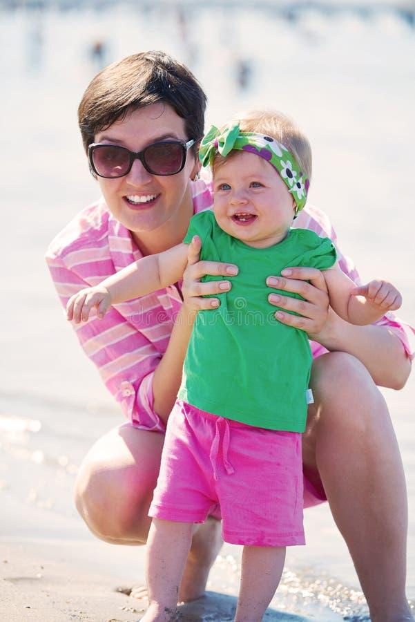 La mamá y el bebé en la playa se divierten imagen de archivo